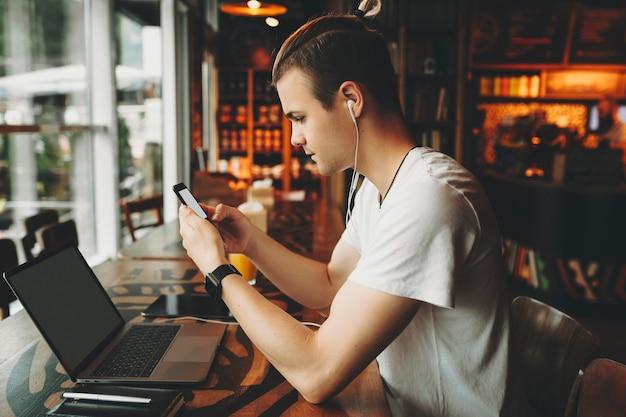 Widok Z Boku Siedzenia Przy Wysokim Drewnianym Stole W Oknie Młody Atrakcyjny Mężczyzna Z Kreatywną Fryzurą W Letniej Koszuli I Słuchawkach Tekstowych Na Ekranie Telefonu Komórkowego W Rękach Premium Zdjęcia