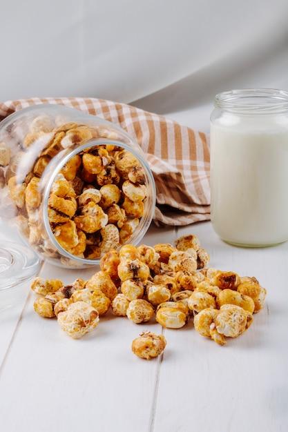 Widok Z Boku Słodkiego Popcornu Karmelowego Rozrzucone Ze Szklanego Słoika Na Białym Stole Darmowe Zdjęcia