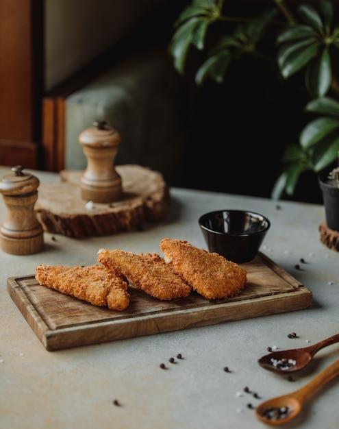 Widok Z Boku Smażonego Fileta Z Kurczaka W Bułce Tartej Z Sosem Na Desce Darmowe Zdjęcia