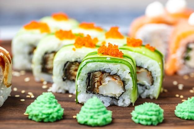 Widok Z Boku Smoczej Bułki Z Ogórkiem Smażone Ryby Tobiko Kawior Nasiona Sezamu I Wasabi Na Pokładzie Darmowe Zdjęcia