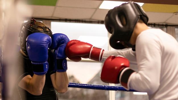 Widok Z Boku Trenującego Na Ringu Boksera Z Kaskiem Darmowe Zdjęcia