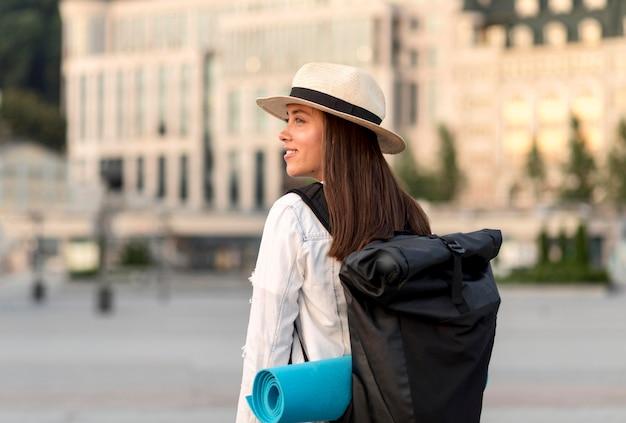 Widok Z Boku Uśmiechniętej Kobiety Podróżującej Samotnie Z Plecakiem Darmowe Zdjęcia