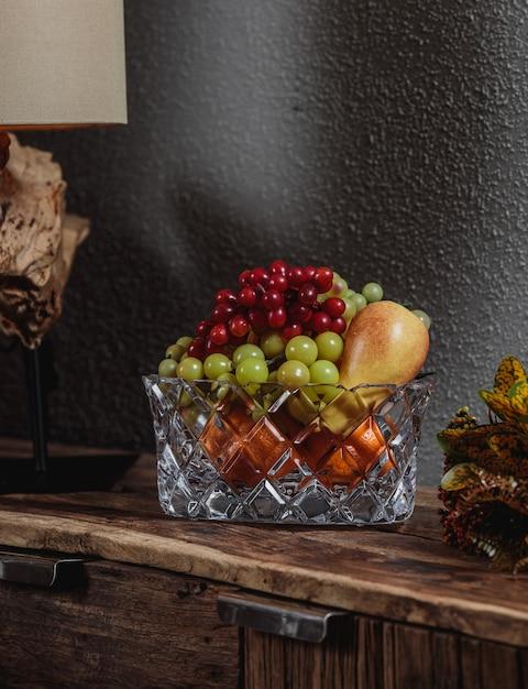 Widok Z Boku Winogron Z Gruszkami W Szklanej Wazonie Na Drewnianej Szafce Na Ciemnej ścianie Darmowe Zdjęcia