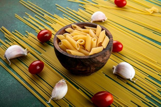 Widok Z Boku Z Surowego Spaghetti Z Makaronem W Misce Pomidorkami Cherry I Czosnkiem Na Zielonej Powierzchni Darmowe Zdjęcia
