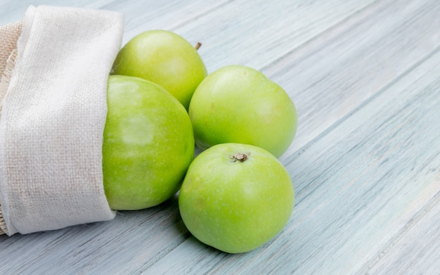 Widok Z Boku Zielonych Jabłek Wysypujących Się Z Worka Na Powierzchni Drewnianych Z Miejsca Na Kopię Darmowe Zdjęcia