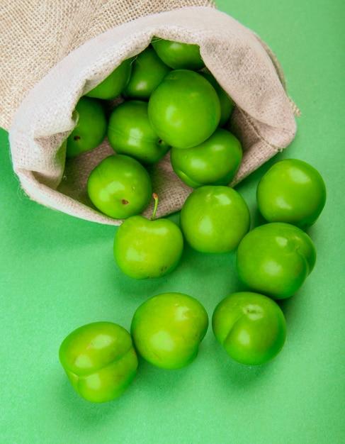 Widok Z Boku Zielonych Kwaśnych śliwek Rozrzuconych Z Worka Na Zielonym Stole Darmowe Zdjęcia