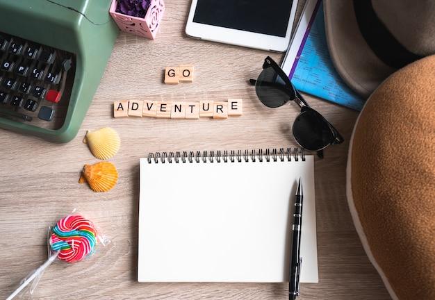Widok Z Góry Akcesoria Podróżnicze Z Pustą Książkę I Słowa Przygoda Go Napisany Na Drewnianym Klocku Premium Zdjęcia