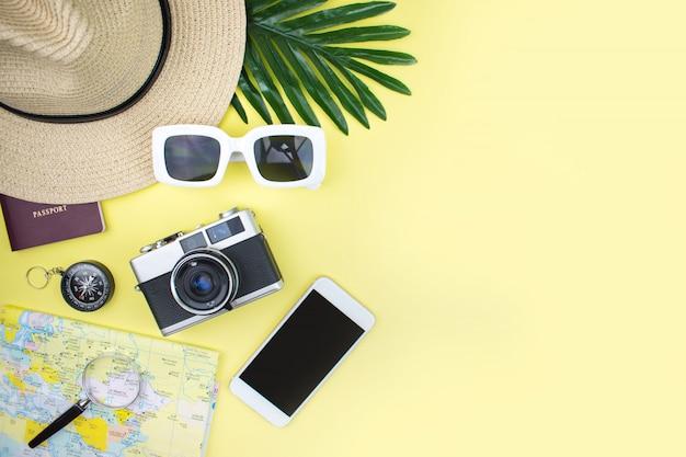 Widok z góry akcesoriów turystycznych z kamer filmowych, map, pasteli, czapek, okularów przeciwsłonecznych i smartfonów na żółtym tle Premium Zdjęcia