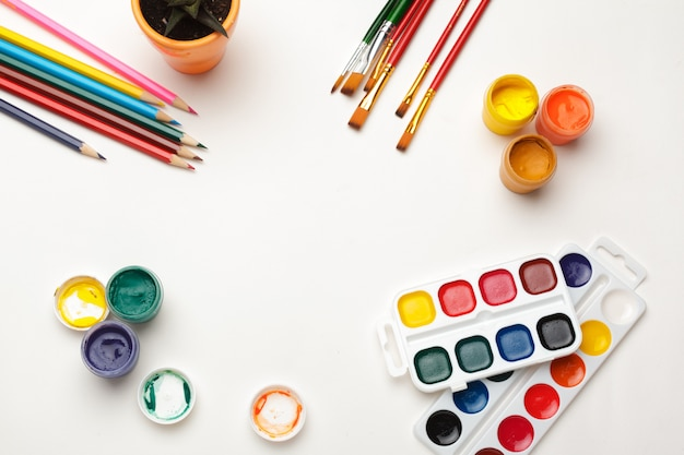 Widok z góry akwareli, pędzli i kolorowy ołówek. proces tworzenia akwareli. skopiuj miejsce Premium Zdjęcia