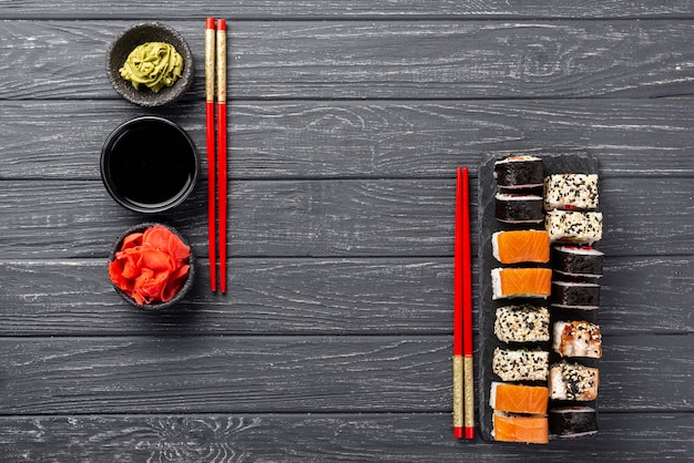 Widok z góry asortyment maki sushi na łupku pałeczkami Darmowe Zdjęcia