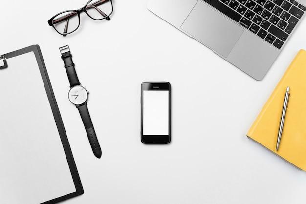 Widok Z Góry Białe Biurko Z Laptopem, Telefonem, Jasne Puste Miejsce Na Papier I Materiały Eksploatacyjne Premium Zdjęcia