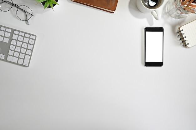 Widok Z Góry Biurka Makieta Smartphone, Klawiatura Komputerowa, Kawa, Notatnik Papier Na Białym Stole. Premium Zdjęcia
