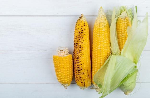 Widok Z Góry Całych I Ciętych Kolb Kukurydzy Na Drewnianej Powierzchni Z Miejsca Kopiowania Darmowe Zdjęcia