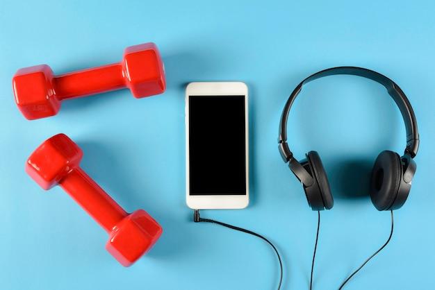 Widok z góry czerwone hantle, czarne słuchawki i inteligentny telefon. koncepcja muzyki, sportu i fitness. Premium Zdjęcia