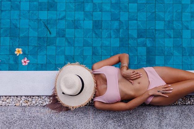 Widok Z Góry Dopasowanie Szczupła Kobieta W Bikini Na Brzegu Basenu, Ciesząc Się Wakacjami Darmowe Zdjęcia