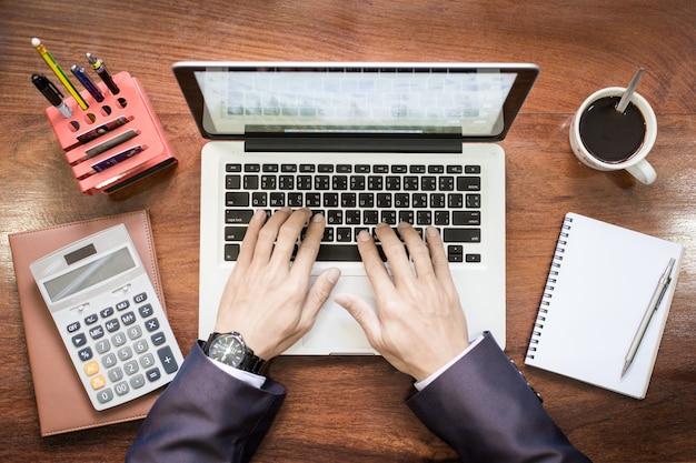 Widok Z Góry Działalności Człowieka Rąk Pracy Na Komputerze Przenośnym Lub Tabletu Pc Na Drewniane Biurko. Darmowe Zdjęcia