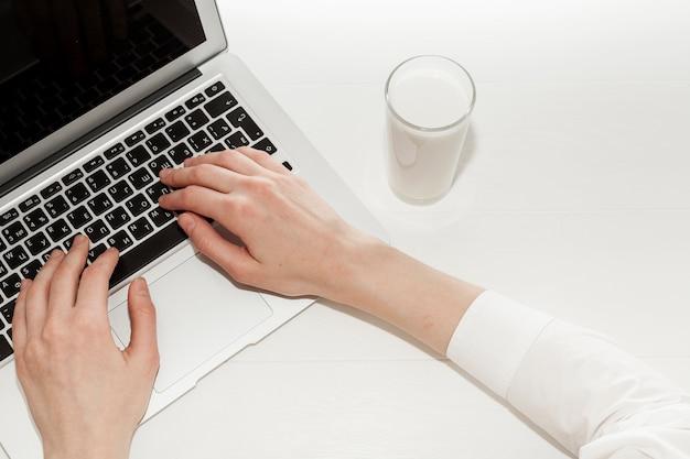 Widok Z Góry Dziewczyna Pracuje Na Swoim Laptopie Obok Szklanki Mleka Darmowe Zdjęcia