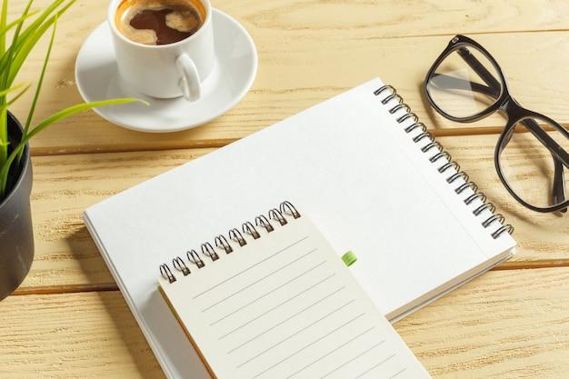 Widok z góry. filiżanka kawy z kawą. pisanie na pustym notatniku. Premium Zdjęcia