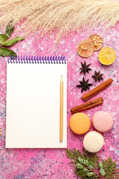 Widok Z Góry Francuskie Macarons Z Notatnikiem Na Różowej Powierzchni Darmowe Zdjęcia