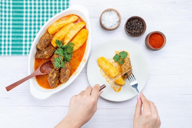 Widok Z Góry Gotowanych Kotletów Mięsnych Z Sosem Ziemniaczanym I Zielonym Jedzeniem Przez Kobietę Na Lekkim Biurku, Posiłek Mięsny Warzywny Darmowe Zdjęcia