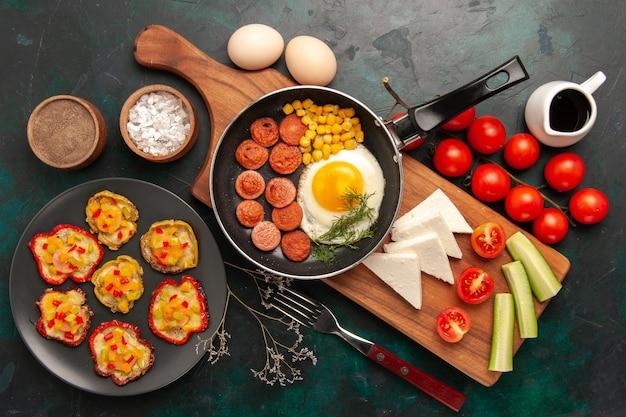 Widok Z Góry Jajecznica Z Plastrami Kiełbasy świeże Pomidory I Surowe Jajka Na Ciemnym Tle Darmowe Zdjęcia
