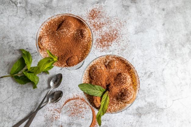 Widok Z Góry Klasycznego Deseru Tiramisu Z Kakao I Ciasteczkami Savoyardi W Szklanych Jagodach I Mięcie Na Szaro Premium Zdjęcia