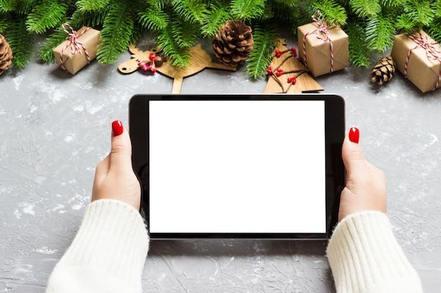 Widok z góry kobiece ręce trzymając tabletkę na cement boże narodzenie wykonane jodły i świąteczne dekoracje. święto nowego roku. makieta Premium Zdjęcia