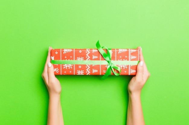 Widok Z Góry Kobiecych Rąk, Trzymając W Dłoniach Boże Narodzenie Lub Inne Wakacyjne Ręcznie Robione Pudełko Prezent Premium Zdjęcia