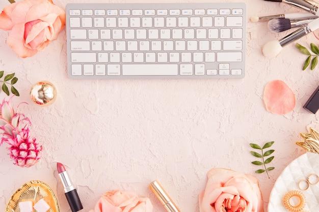 Widok z góry kobiety blogger pracy biurko z klawiaturą komputera i laptopa, kosmetyk dekoracyjny, kwiaty i liście palmowe Premium Zdjęcia