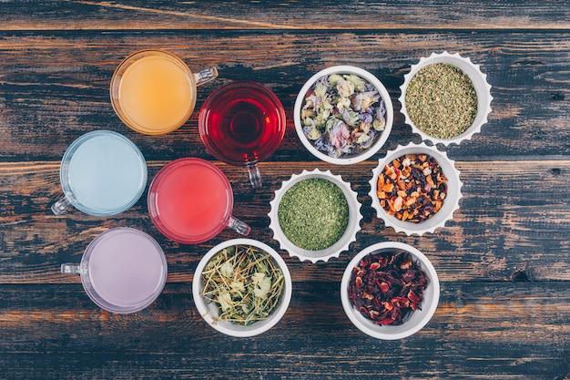 Widok Z Góry Kolorowe Rodzaje Wody I Herbaty W Filiżankach I Miseczkach Na Ciemnym Tle Drewniane. Poziomy Darmowe Zdjęcia