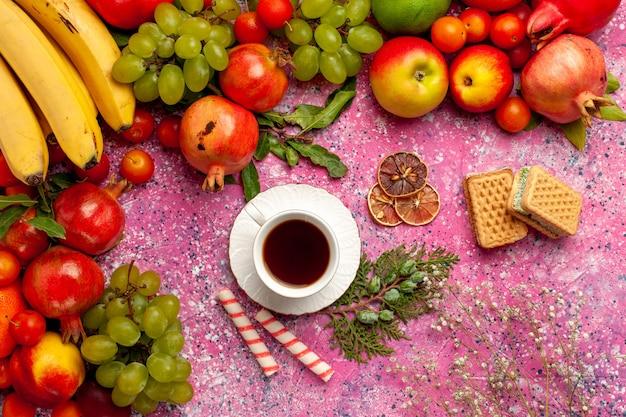 Widok Z Góry Kompozycja świeżych Owoców Kolorowe Owoce Z Goframi I Filiżanką Herbaty Na Różowej Powierzchni Darmowe Zdjęcia