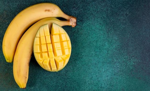 Widok Z Góry Kopia Przestrzeń Banany Z Posiekanymi Mango Na Zielono Darmowe Zdjęcia