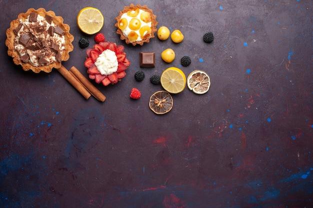 Widok Z Góry Kremowych Ciast Z Owocami I Konfiturami Jagodowymi Na Ciemnofioletowej Powierzchni Darmowe Zdjęcia