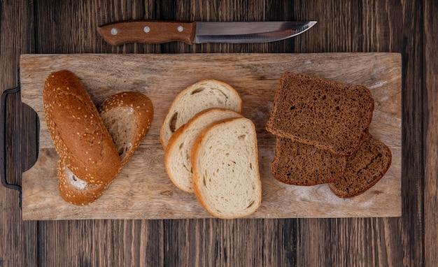 Widok Z Góry Krojonego Chleba Jako Zasiane Brązowe Kolby Białe I żytnie Na Deska Do Krojenia I Nóż Na Podłoże Drewniane Darmowe Zdjęcia