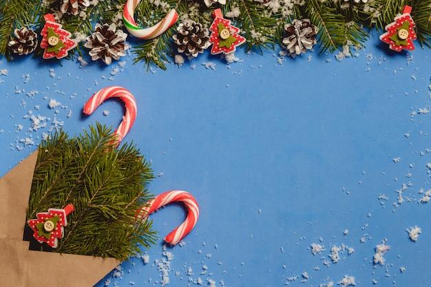 Widok z góry laski cukierków i szpilki w kształcie czerwonej jodły w brązowej kopercie rzemieślniczej Premium Zdjęcia