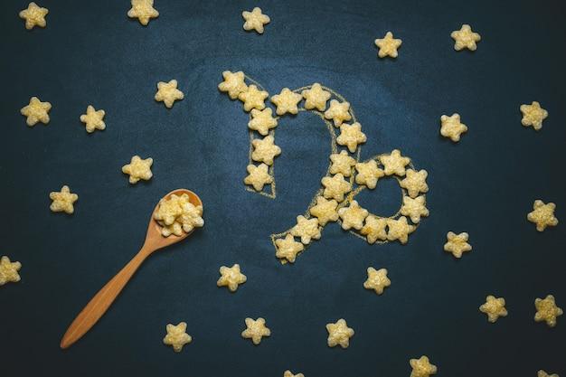 Widok Z Góry Leżał Koziorożec, Znak Horoskopu Wykonany Z Chrupiących Gwiazd Kukurydzy Na Czarnym Tle Premium Zdjęcia