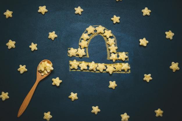 Widok Z Góry Leżał Libra, Znak Horoskopu Wykonany Z Chrupiących Gwiazd Kukurydzy Na Czarnym Premium Zdjęcia