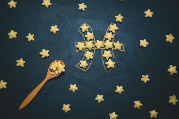 Widok Z Góry Leżał Płasko Ryby, Znak Horoskopu Wykonany Z Chrupiących Gwiazd Kukurydzy Na Czarnym Premium Zdjęcia