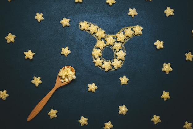 Widok Z Góry Leżał Znak Horoskopu Baran Wykonany Z Chrupiących Gwiazd Kukurydzy Na Czarnym Tle Premium Zdjęcia
