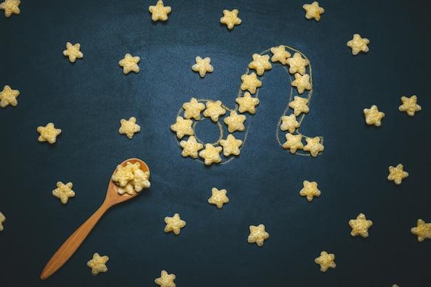 Widok Z Góry Leżał Znak Horoskopu Leo Wykonany Z Chrupiących Gwiazd Kukurydzy Na Czarnym Tle Premium Zdjęcia