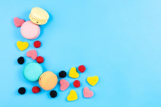 Widok Z Góry Macarons I Marmelades Kolorowe Francuskie Ciasta I Cukierki Samodzielnie Na Niebieskim Tle Kolorowe Tå'o Cukier Słodkie Ciasto Darmowe Zdjęcia