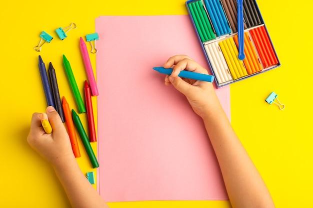 Widok Z Góry Małe Dziecko Za Pomocą Kolorowych Ołówków Na Różowym Papierze Na żółtej Powierzchni Darmowe Zdjęcia