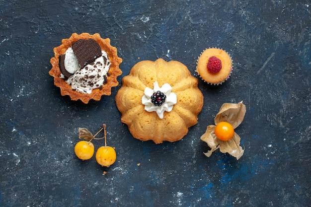 Widok Z Góry Małe Pyszne Ciasto Wraz Z Ciasteczkiem Na Ciemnym Tle Biszkoptowe Ciasto Słodkie Owoce Darmowe Zdjęcia