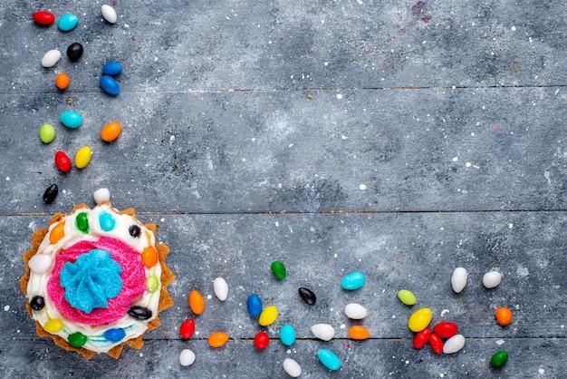 Widok Z Góry Małe Pyszne Ciasto Z Kremem I Różnymi Kolorowymi Cukierkami Na Jasnym Tle Cukierki Słodki Kolor Zdjęcie Ciasta Darmowe Zdjęcia