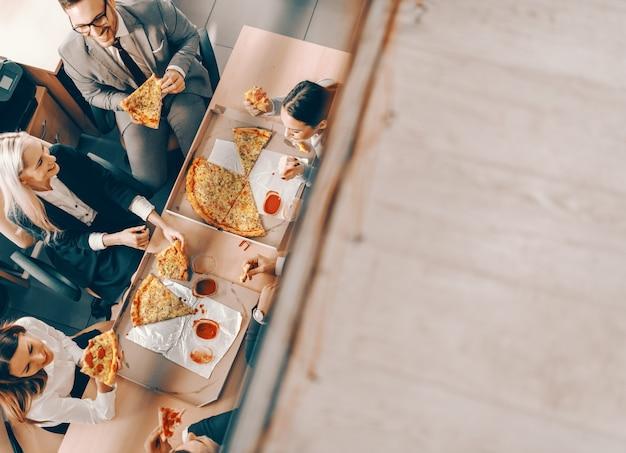 Widok Z Góry Małej Grupy Ludzi Biznesu Jedzących Pizzę Na Obiad. życie Jest Dobre, Robisz Je Dobre. Premium Zdjęcia