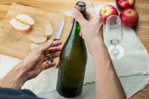 Widok Z Góry Męskich Rąk Trzyma Zakorkowaną Butelkę Premium Cidre. Strzał Z Góry Piękną Lodową Butelką Wina Jabłkowego W Rękach Mężczyzny Premium Zdjęcia