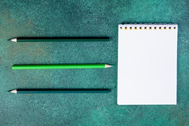 Widok Z Góry Miejsca Kopiowania Ołówki Zielony Odcień Z Notatnikiem Na Zielonym Tle Darmowe Zdjęcia