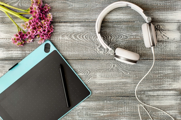 Widok Z Góry Miejsce Pracy Z Cyfrowym Tabletem I Długopisem Graficznym, Słuchawki I Kwiat Premium Zdjęcia