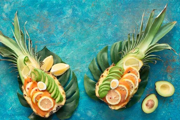 Widok Z Góry Na Ananasowe łódki Z Wędzonym łososiem I Plastry Awokado Z Jajkami Cytrynowymi I Przepiórczymi Premium Zdjęcia