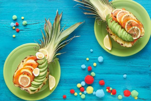 Widok Z Góry Na Ananasowe łódki Z Wędzonym łososiem I Plastry Awokado Z Jajkami Cytryny I Przepiórki Premium Zdjęcia